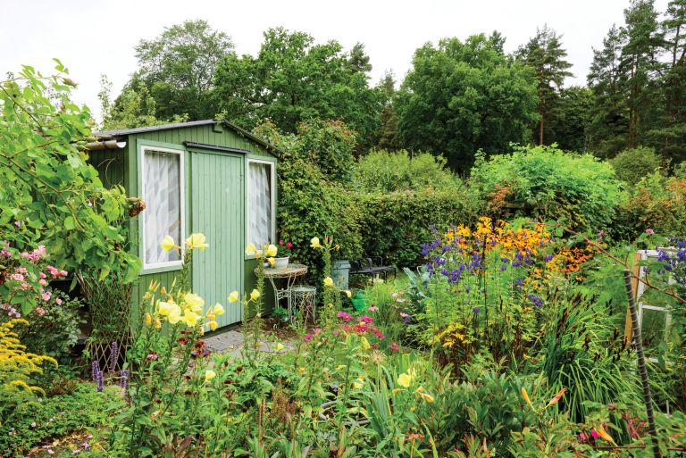 a painted shed in a country garden with lots of flowrrs