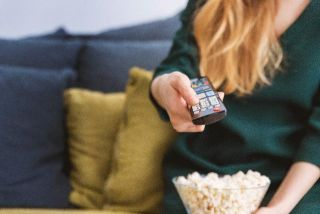 Woman with popcorn and remote