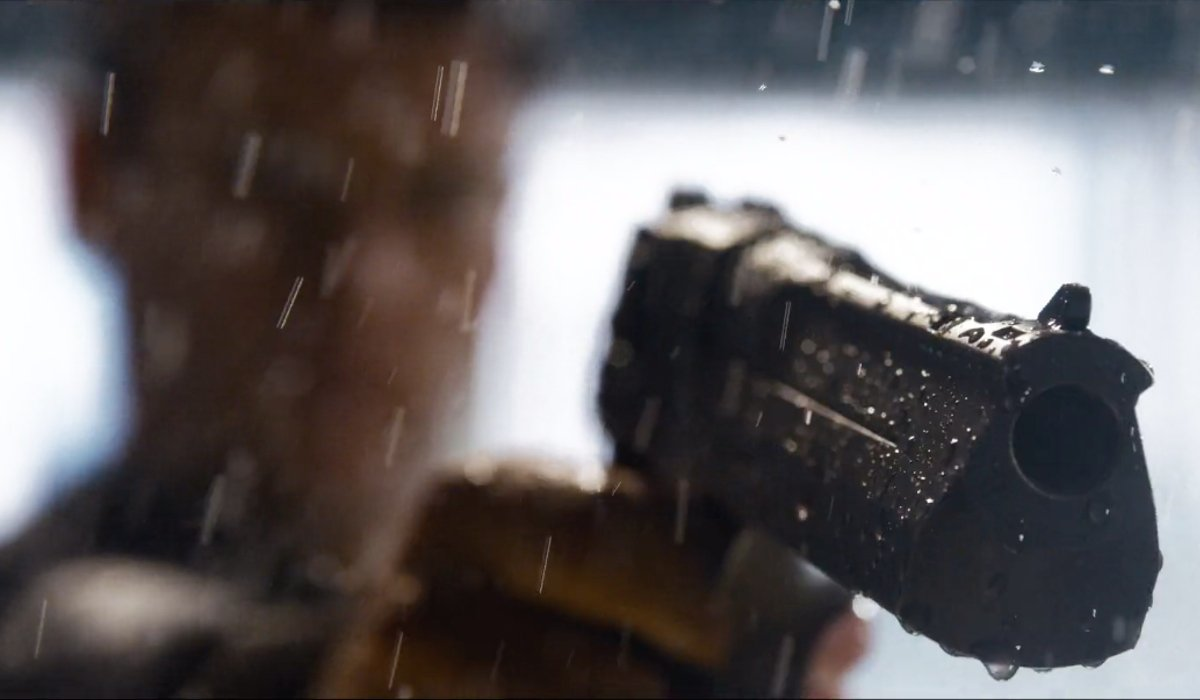 An obscured figure aiming a gun in The Matrix Resurrections.