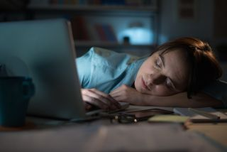 A woman falls asleep at her desk after working