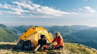 A couple camping on a mountain top
