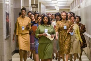 A large group of women walks down a hallway