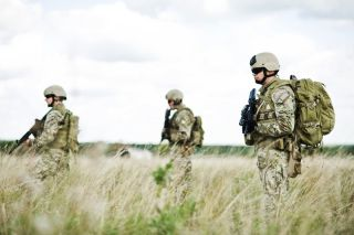 Three soldiers stand in a field.