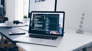 website audit - laptop on desk in front of a monitor, with the laptop displaying code
