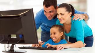 A family using a PC and looking at the monitor