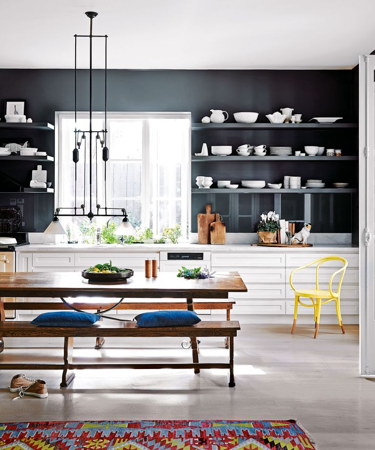 An example of kitchen storage ideas showing an open plan kitchen with white cabinets and a black wall with a wooden dining bench