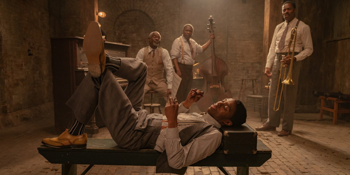 Chadwick Boseman lying on a bench in front of his band mates in Ma Rainey's Black Bottom.