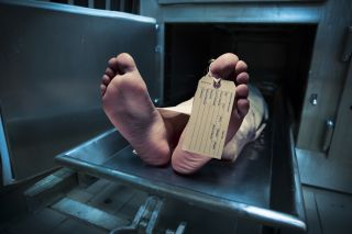 Photo of feet with toe tag, lying on a morgue table.