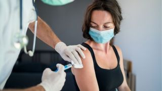 woman in face mask receiving vaccine