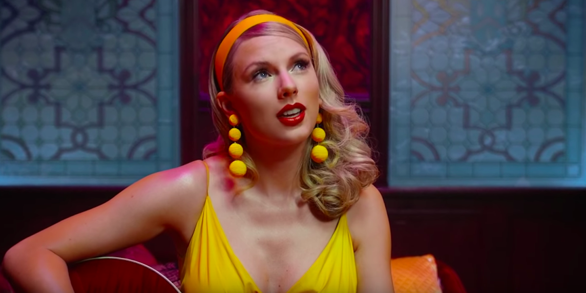 Taylor Swift wearing yellow earring and dress and playing the guitar in the Lover music video