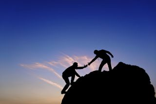 A figure in silhouette atop a mountain extends a hand to help another climber.
