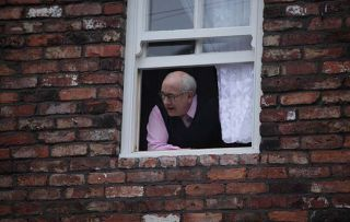 Norris Cole pokes his head out of number three Coronation Street