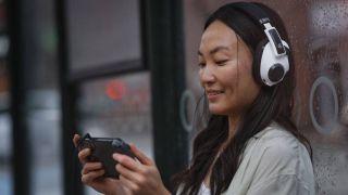 Woman playing Nintendo Switch while wearing the Epos H3 Hybrid
