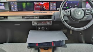PS5 in Honda e with Deathloop on screen