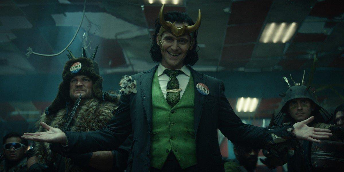 "Loki (Tom Hiddleston) smiles and stands among his ""allies"" on Loki (2021)"