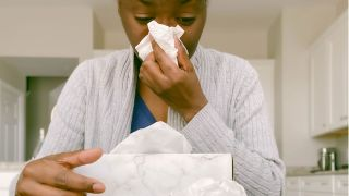 Do humidifiers help with allergies? Image shows woman blowing her nose with a tissue