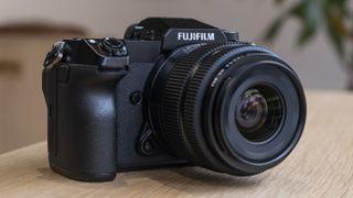 The Fujifilm GFX50S II camera on a wooden table