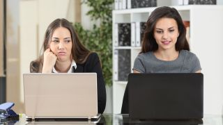 two women using laptops