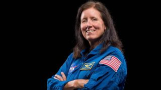Photo of NASA astronaut Shannon Walker in a blue flight suit with American flag patch on the sleeves. She is crossing her arms and smiling at the camera.