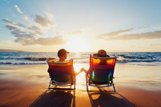 A couple relaxes in their beach chairs in front of a sunset
