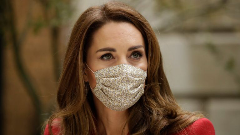 Wearing a face covering to curb the spread of coronavirus, Catherine, Duchess of Cambridge meets pharmacist Joyce Duah as she and Prince William visit St. Bartholomew's Hospital in London, to mark the launch of the nationwide 'Hold Still' community photography project
