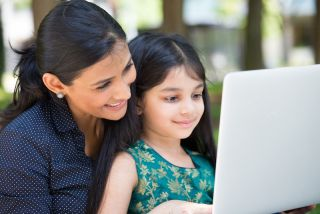 A mom and her daughter look at a laptop screen together.