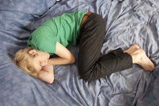Blond teen boy lying in bed sad.