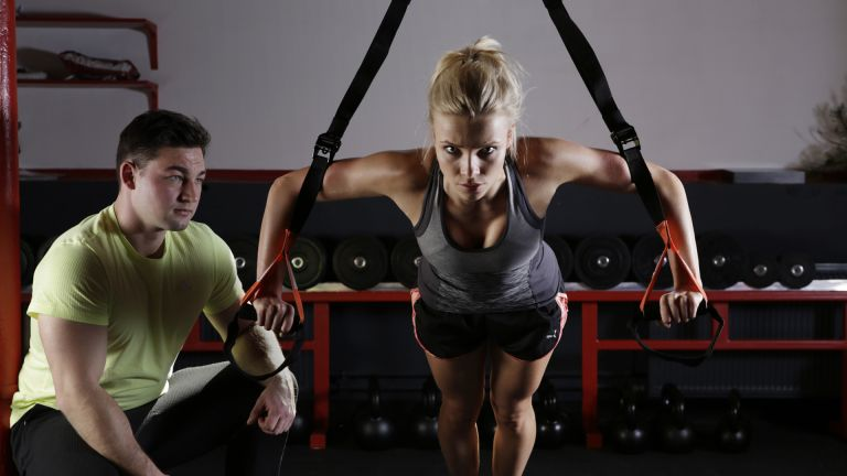 Woman working out her arms using a TRX set up