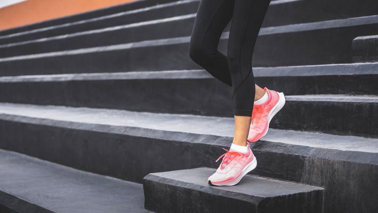 Woman in black leggings running down stairs