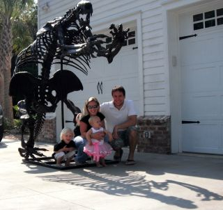 Commercial paleontologist Eric Prokopi of Gainesville, Florida with his wife, Amanda, and their two children in front of one of his earlier restoration projects, the skeleton of a giant ground sloth.