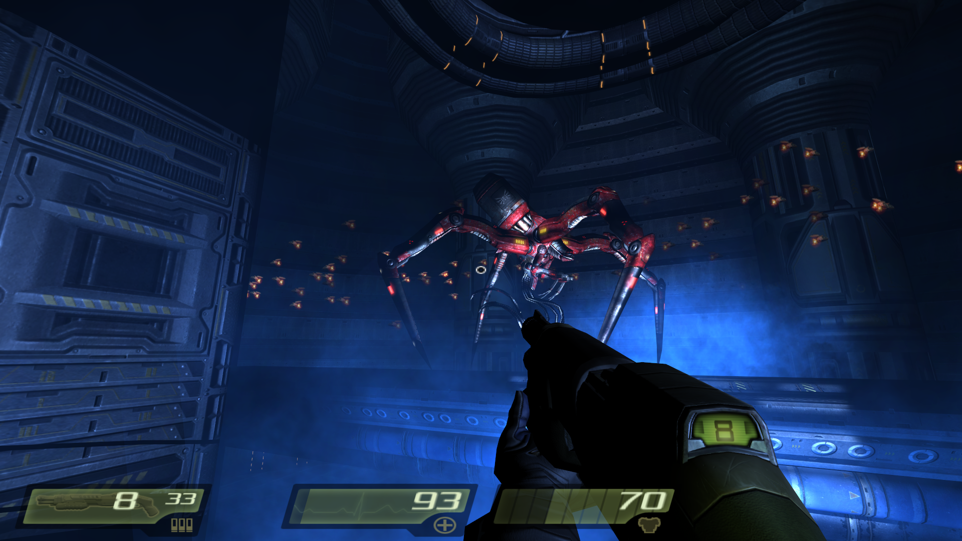 A giant red spiderbot stalks the player through a Strogg facility