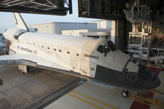 Space shuttle Discovery rolls March 9, 2011 into Kennedy Space Center's Orbiter Processing Facility-2 in Florida after its final mission STS-133. It will be readied for retirement and public display.
