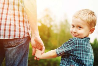 man holding young boy's hand