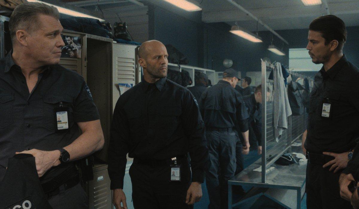 Holt McCallany, Jason Statham, and Josh Hartnett talking in the locker room in Wrath of Man.