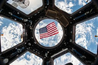 An American flag floats in weightlessness, with the Earth as a magnificent backdrop, in this photo from the Cupola observation room on the International Space Station taken by NASA astronaut Kjell Lindgren.