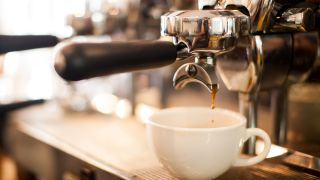 A coffee cup on a espresso machine and coffee starting to brew