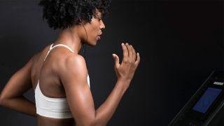 跑步能燃烧脂肪吗?图为一名女子在跑步机上跑步。