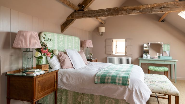 pink and green traditional bedroom with beams
