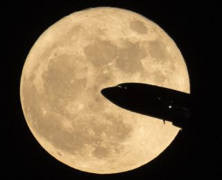 An airplane crosses the supermoon full moon of Dec. 3, 2017 as seen near Ronald Reagon National Airport in Washington, D.C.
