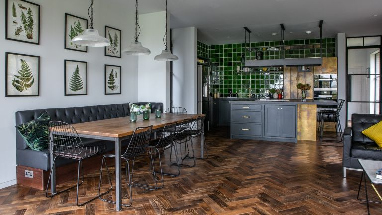 A Victorian. industrial style kitchen with white walls, black dining bench, black cabinetry and green glazed tiles