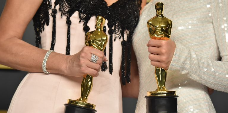 """Laura Dern, winner of the Actress in a Supporting Role award for """"Marriage Story,"""" and Renée Zellweger, winner of the Actress in a Leading Role award for """"Judy,"""" statuette detail, pose in the press room during the 92nd Annual Academy Awards"""
