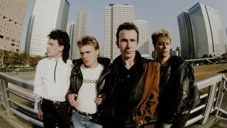 A photograph of U2 surrounded by high-rise buildings in Shinjuku, Tokyo, November 1983