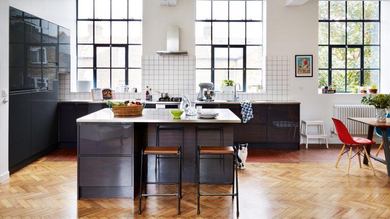 Carlo Viscione: industrial-style kitchen with dark blue units, parquet flooring and grid-pattern white splashback tiles