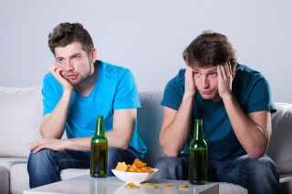 Two guys look bored while watching TV and drinking beer.