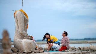 Two women with a young girl between them kneel before a tall, headless, cross-legged statue of Buddha. A cloth is draped over the statue's shoulders. There is shallow water in the background.