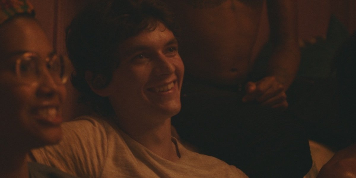 Leyna Bloom and Fionn Whitehead smiling as Wye and Paul at a party in Port Authority