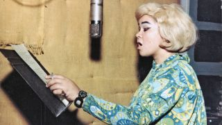 Etta James singing in the studio, holding a cigarette