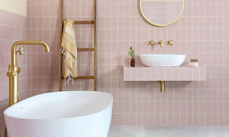 Pink tiled bathroom with white tub, gray flooring and gold accents including a wall mirror