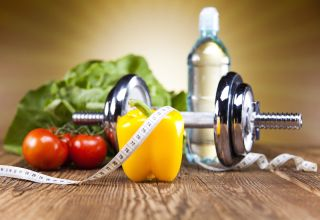An image shows the components of a healthy lifestyle -- vegetables, water, and a dumbell