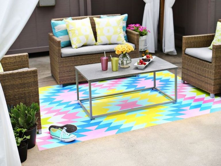 a colourful outdoor rug painted onto concrete in an aztec pattern